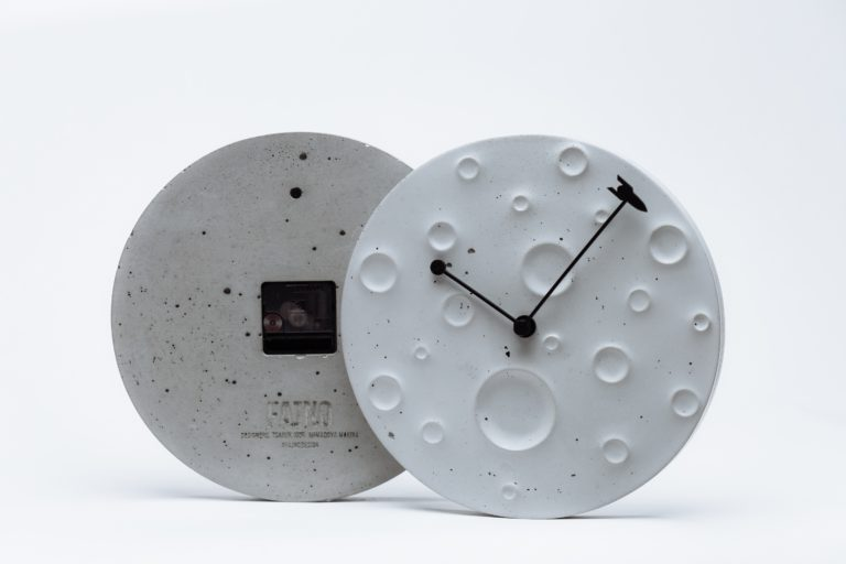 """Wall clock made of concrete in the form of the moon """"Around the Moon in 60 Minutes"""""""